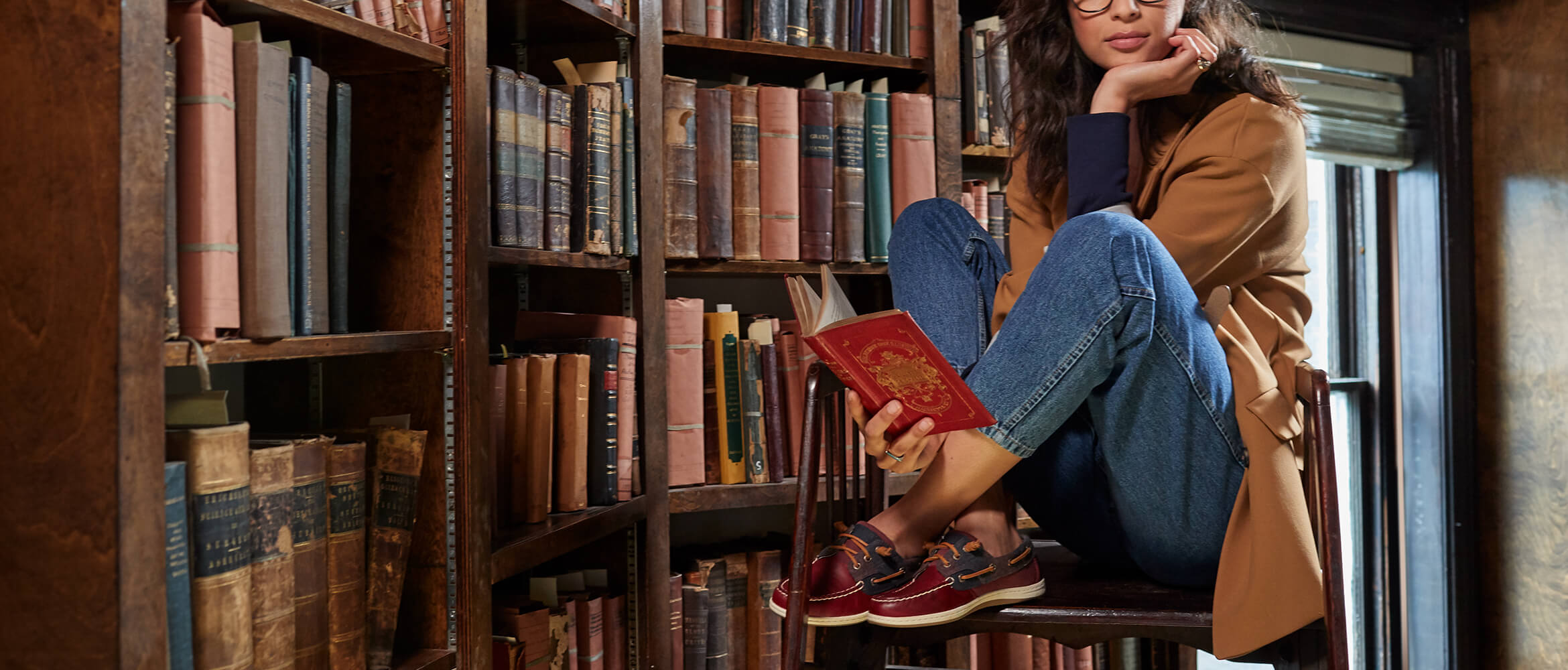 Girl sits on a stool in a library; feet pulled up onto the seat. She holds an open book, but her mind is elsewhere. She has nice shoes.