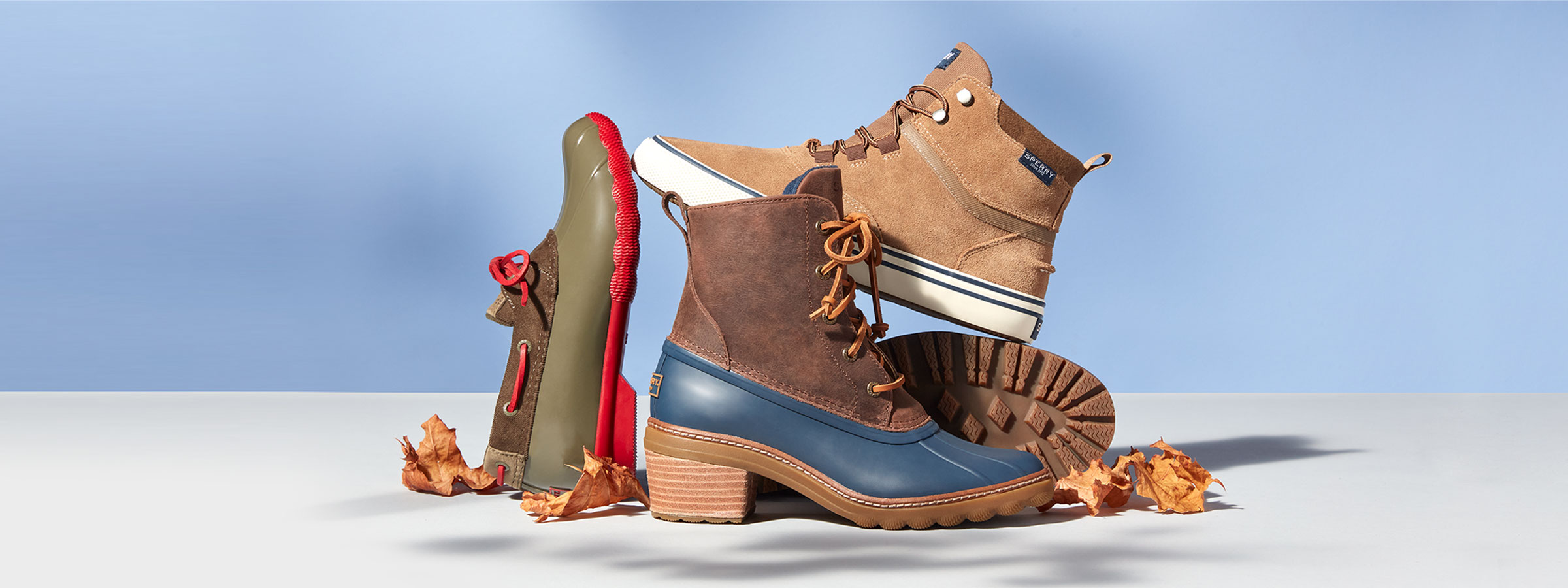 4 Sperry boots propped up on each other surrounded by leaves.