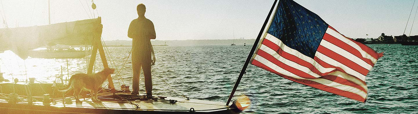 Person stading on a boat with a dog and an American flag waving on the front of the boat.