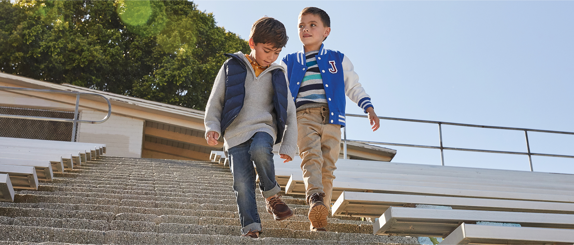 A pair of kids laughing and walking down bleachers with boots and boat shoes.