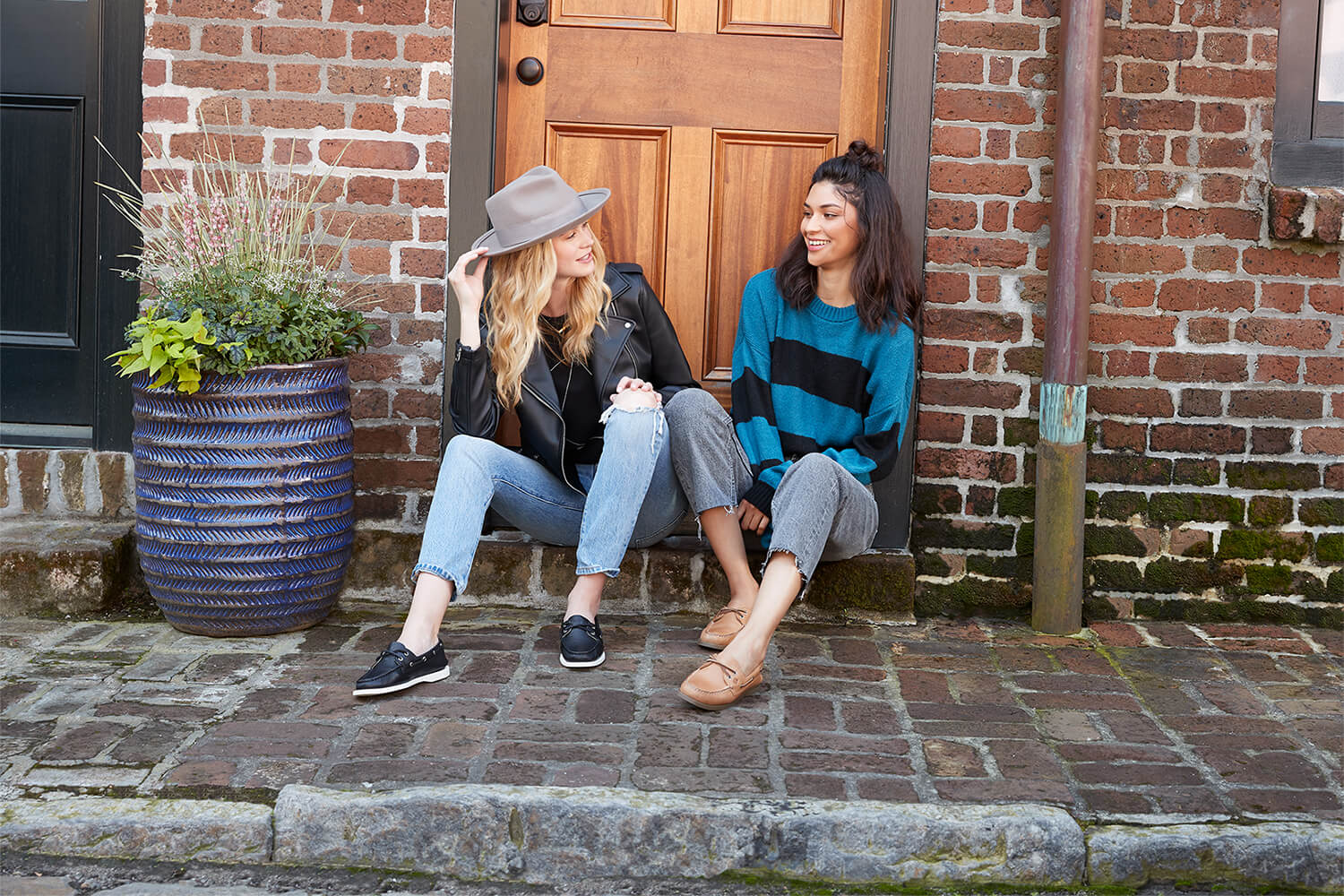 Two women sit in a doorway, laughing. They have nice shoes.