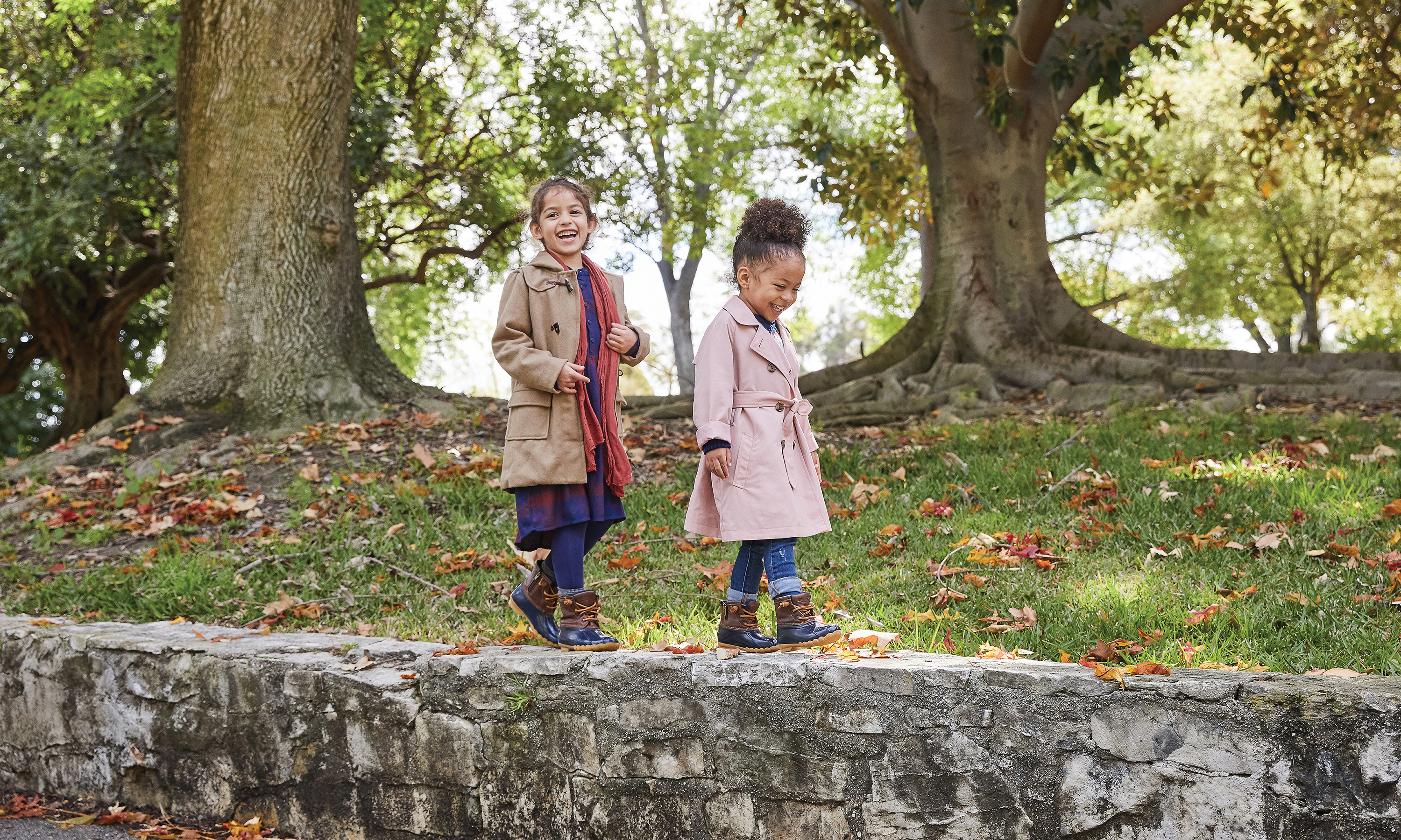 Two girls walking along a stone wall in a park, wearing a wool jackets and Sperry boots.