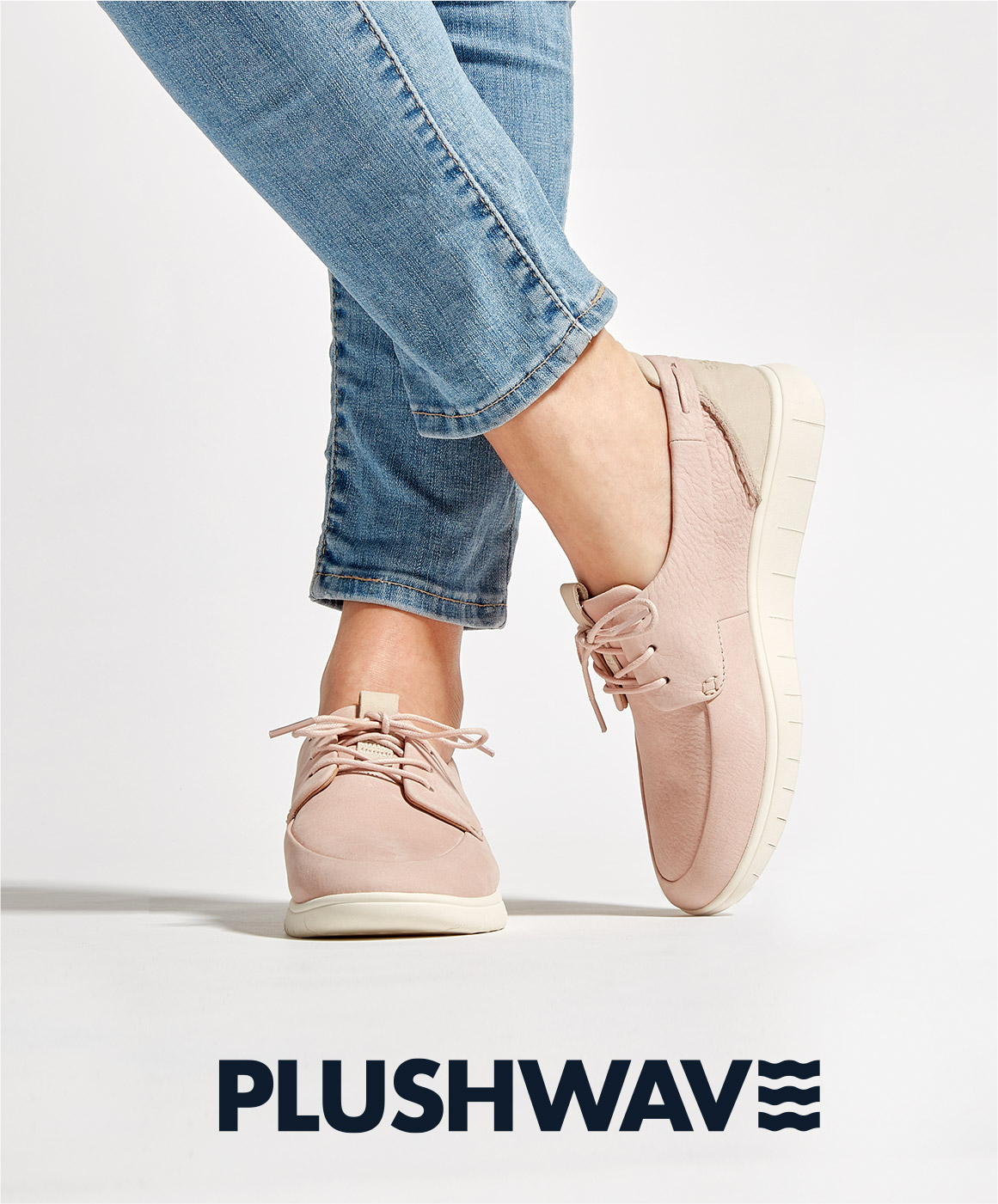 Women crossing her legs with her toe down and heel in the air, and she's wearing comfortable Plushwave Sperrys.