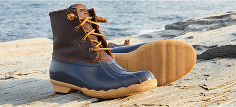 Blue and brown boots on rocks beside water.
