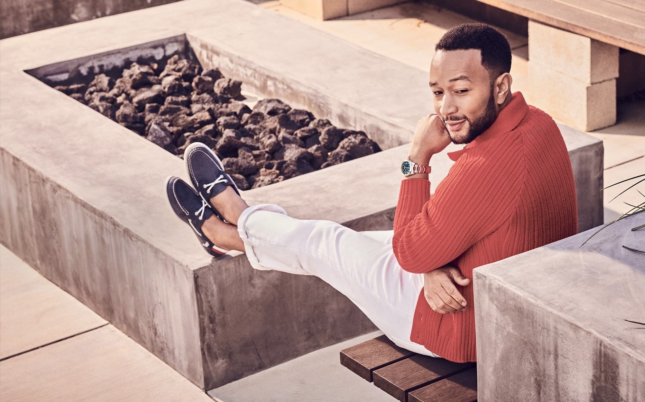 John Legend sitting on a bench, wearing Sperry Boat Shoes.