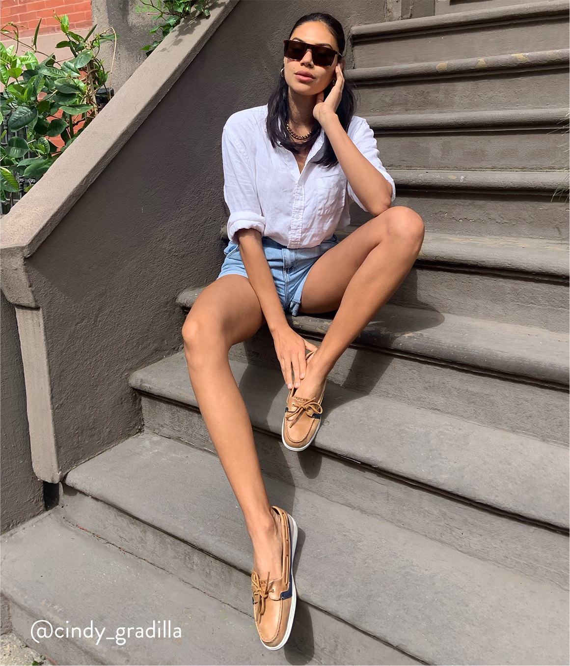 Person sitting on stairs wearing sunglasses and Sperry floats.