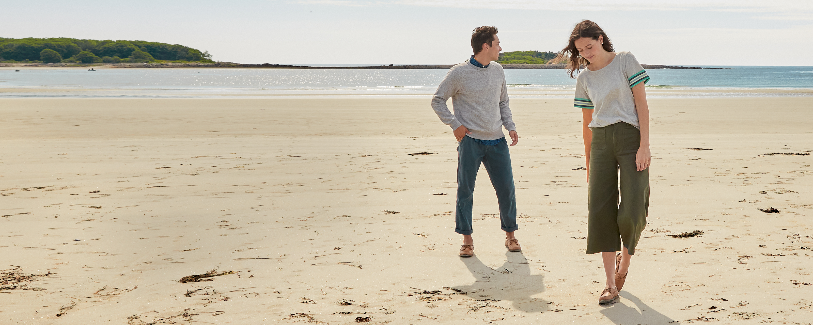 Man and woman walking in classic Sperry shoes on the beach.