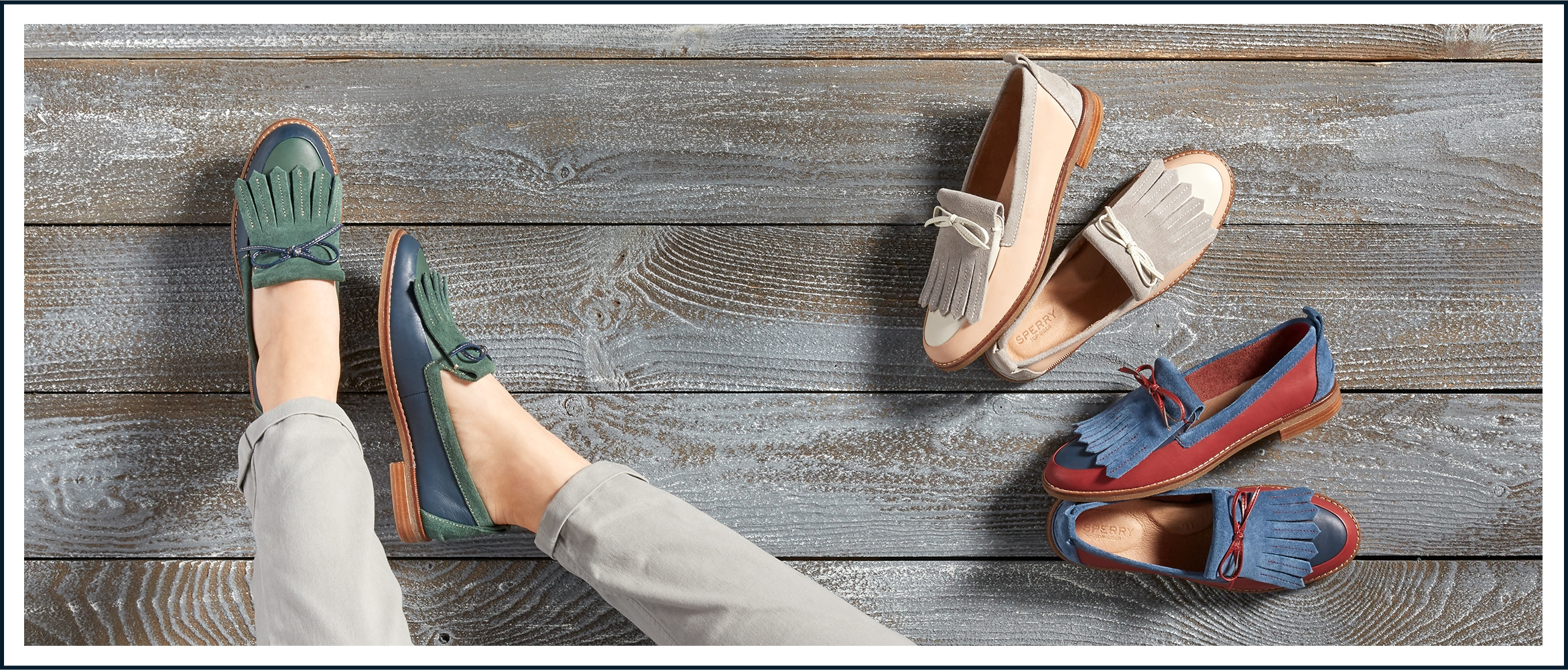 A closeup of one women's feet wearing Seaport Penny Kiltie shoes. Two other pairs are next to her on the deck.
