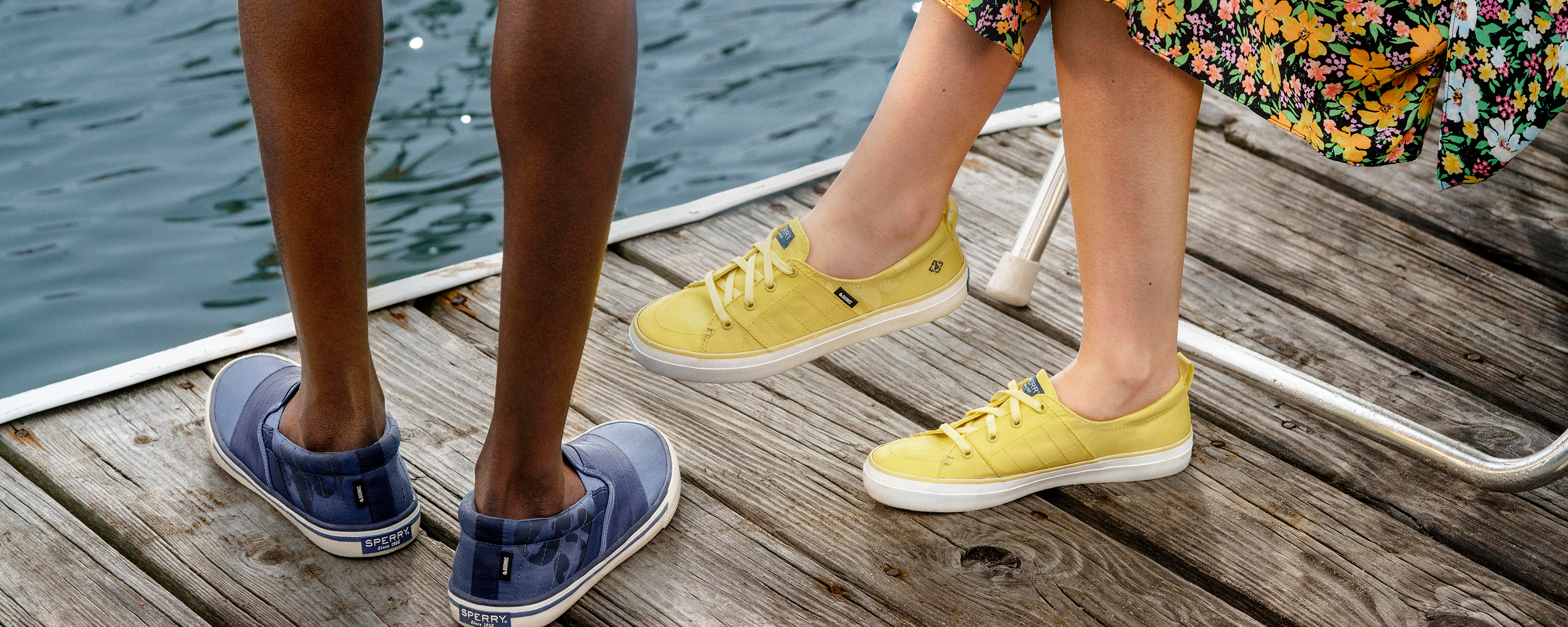 Two people standing on a dock wearing Sperry Bionic sneakers.