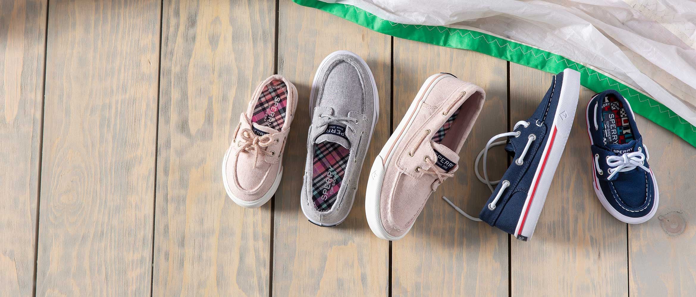 Sperry slip-on shoes of various sizes on a wood floor.