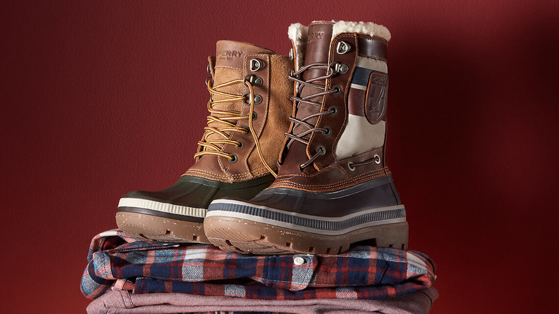 Two boots in different colors stand atop some cozy blankets. Ice Bay? More like Ice Bae!