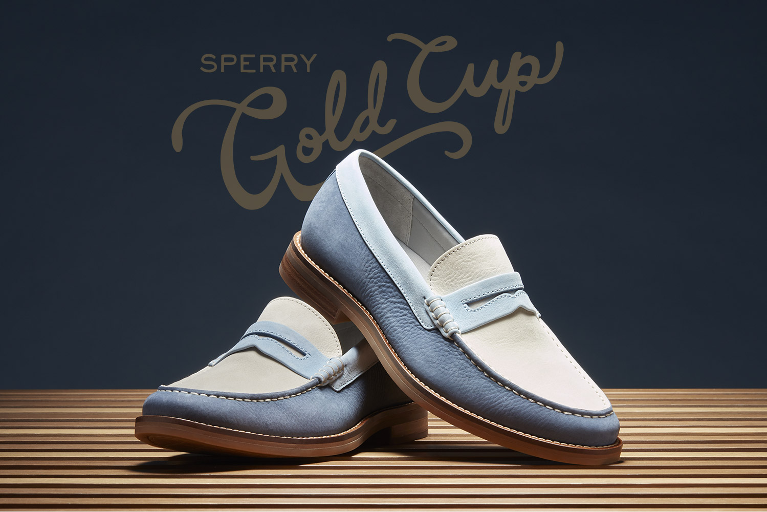 Tri-Toned Blue Leather Gold Cup loafers on a wooden table with a dark blue background