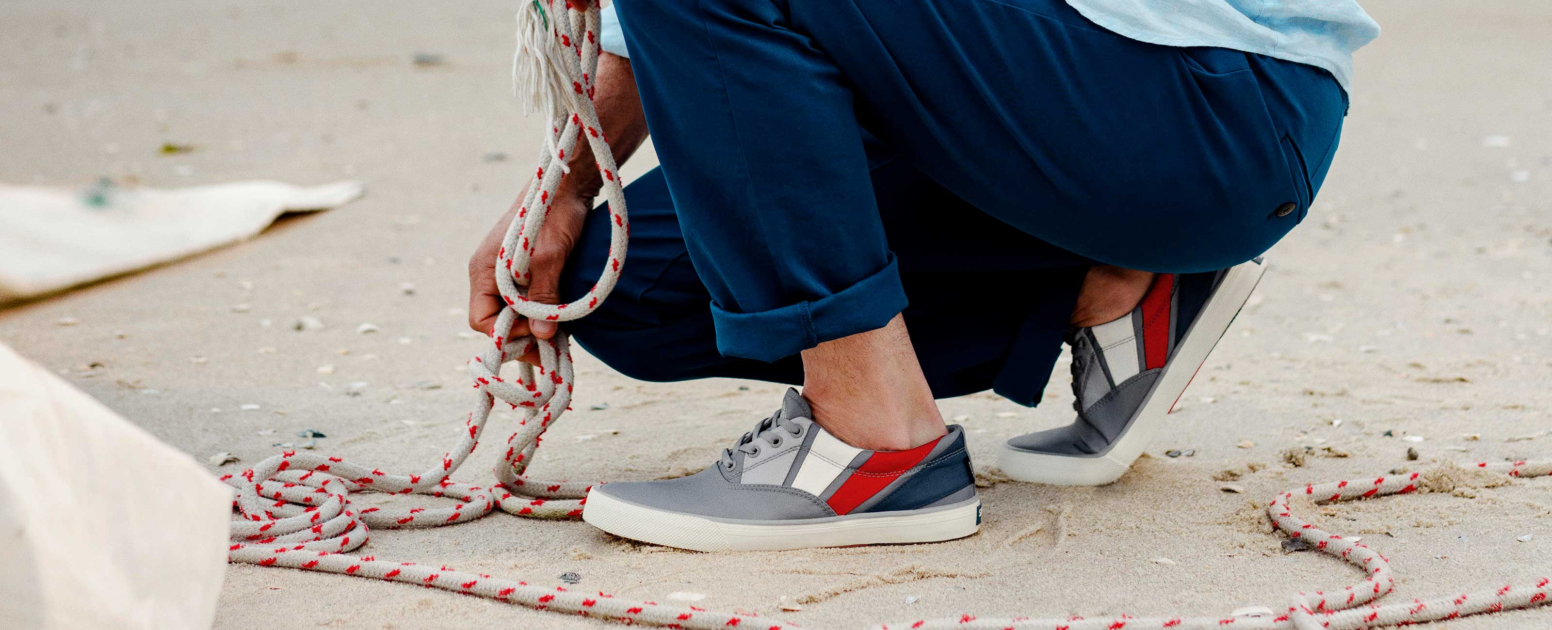 Person kneeled down on a beach, wearing BIONIC Boat Shoes, while attending to a rope from a boat.