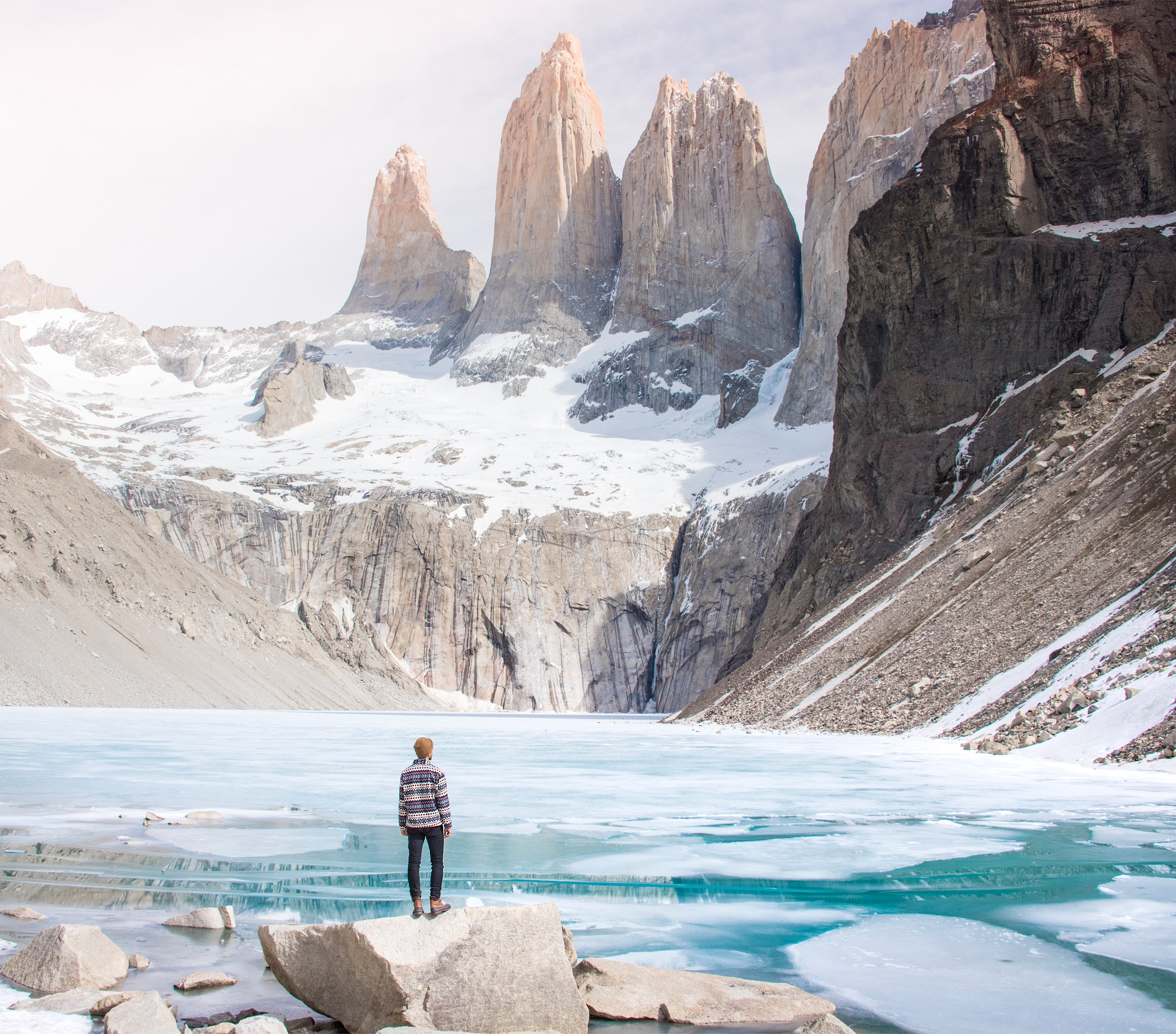 Person standing by an icy mountain lake.