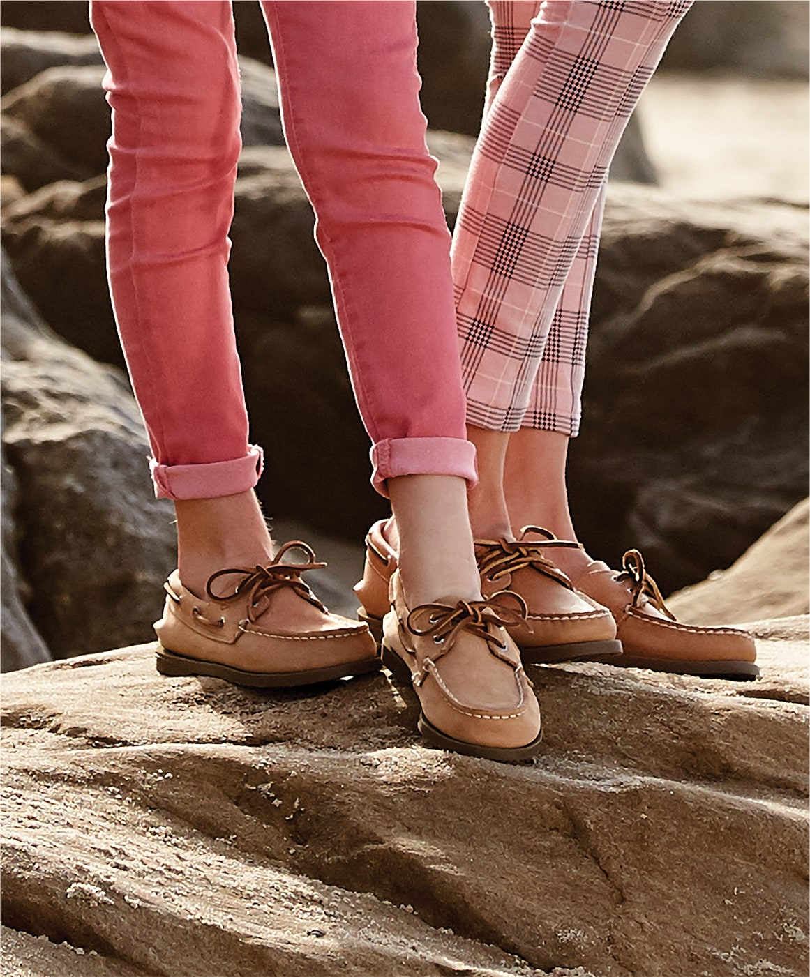 2 kids standing on a rock, wearying Sperry boat shoes.