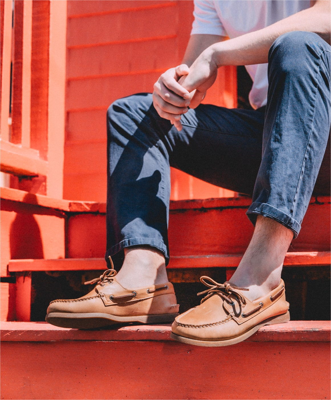 Man sitting on steps, wearing Sperry boat shoes.