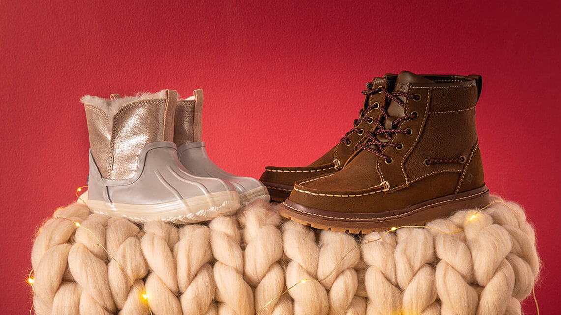 Two pairs of boots sit atop a comfy blanket.