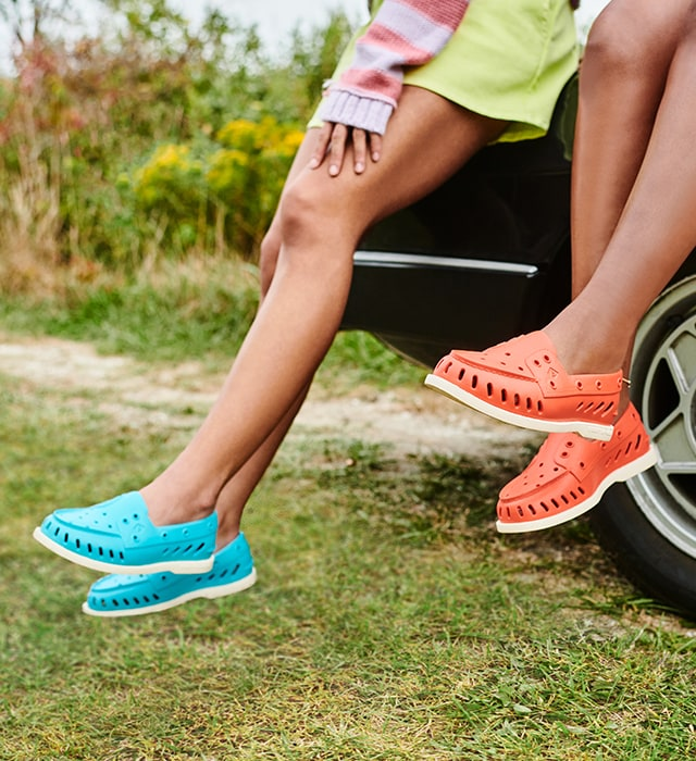 Two people sitting on the hood of a car, both wearing Sperry Float shoes.