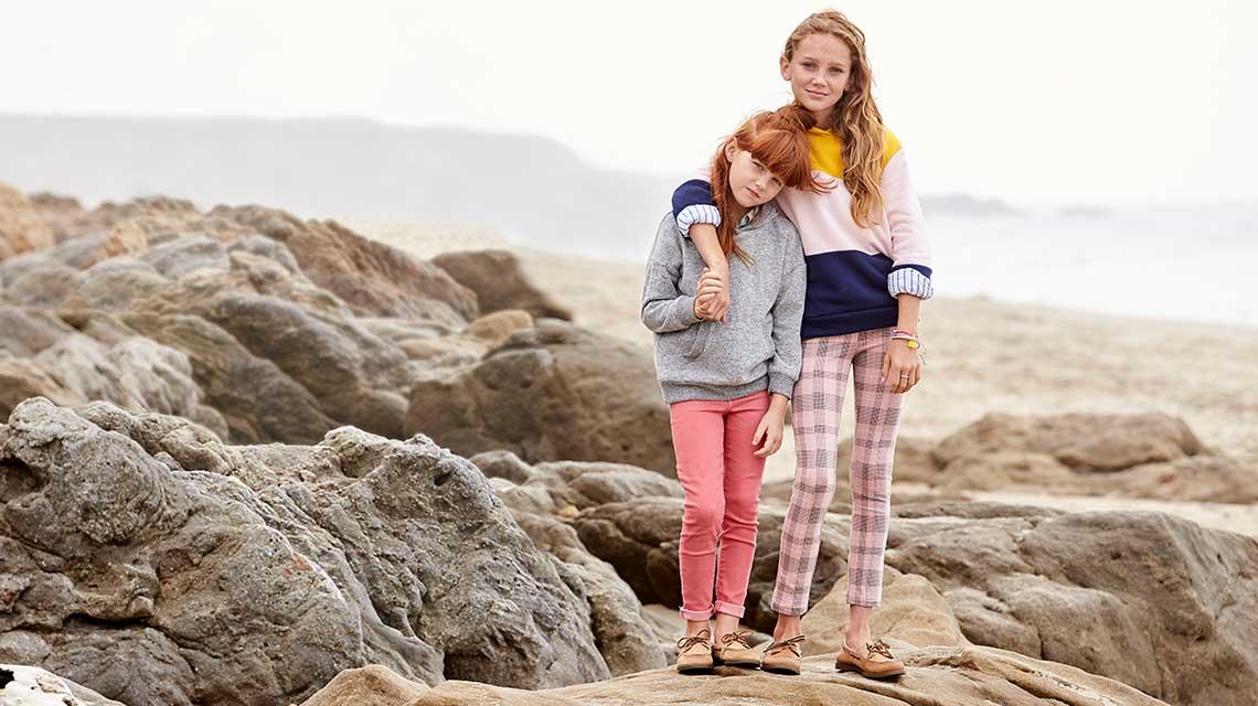 Two girls shoulder to shoulder standing on rocks..