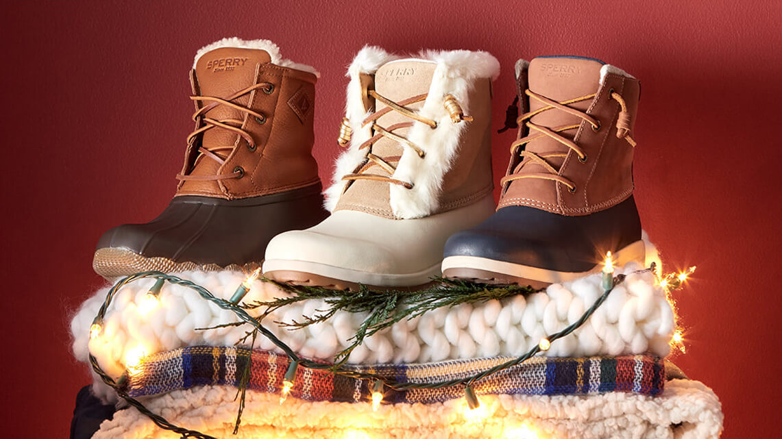 Three boots in different colors stand atop some cozy blankets, wrapped in tree lights. Totes festive!