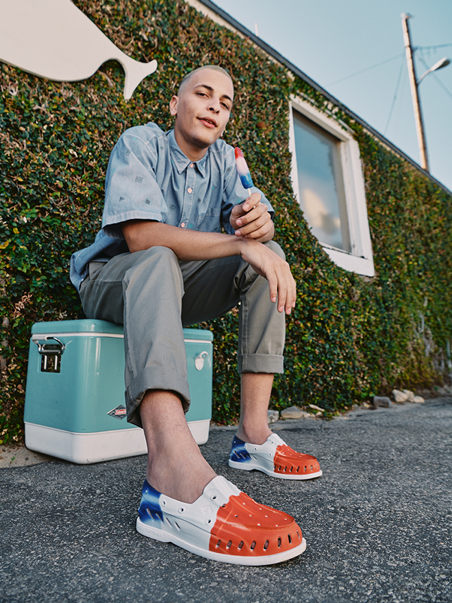 One person sitting on a cooler happily eating ice cream wearing sperry ice cream shoes.