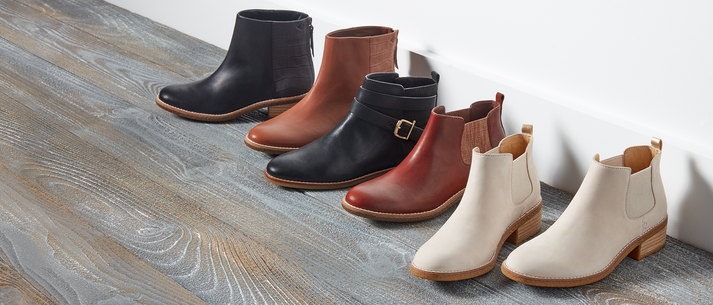 Fashion boots lined up long a white wall with a wood floor.