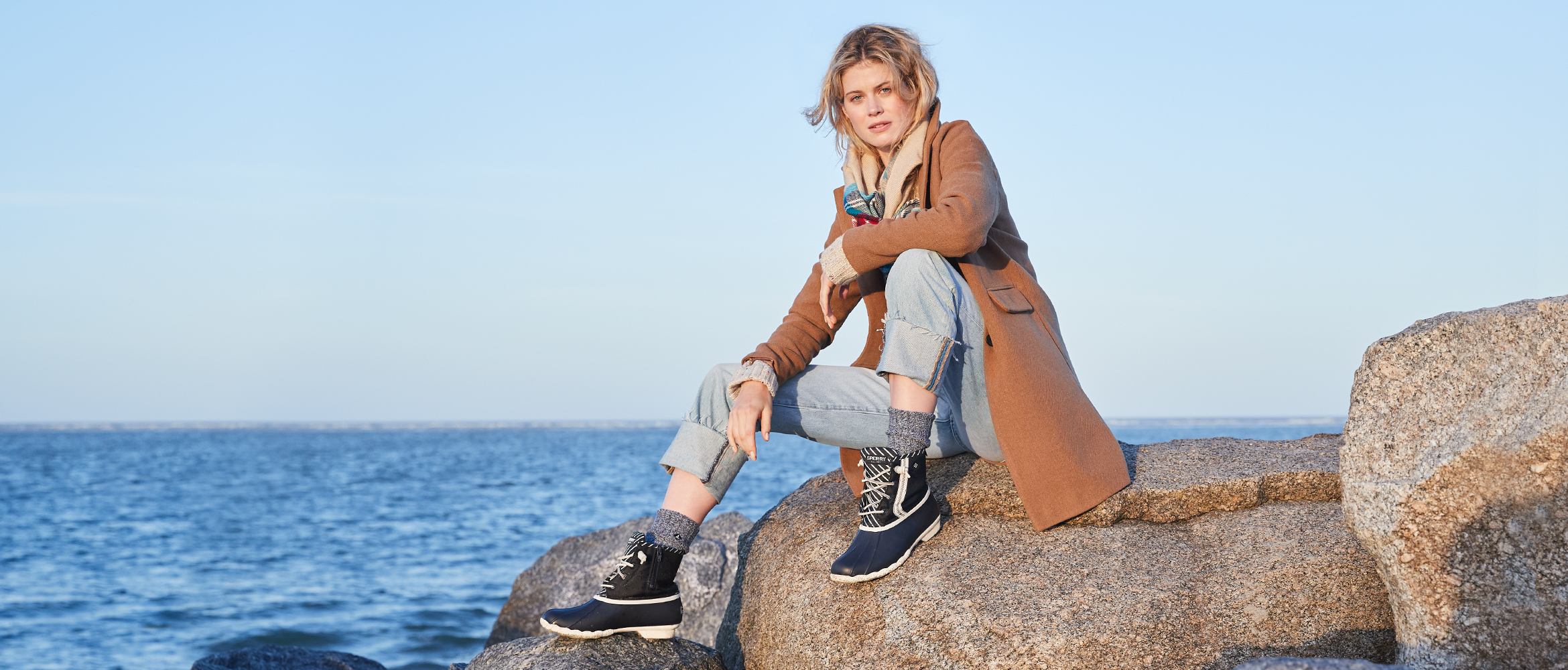 Woman wearing Sperry BIONIC boots while sitting on rocks by the sea.