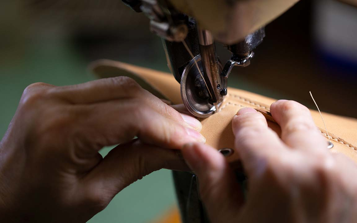 Person Hand Sewing a Sperry Gold Cup shoe.