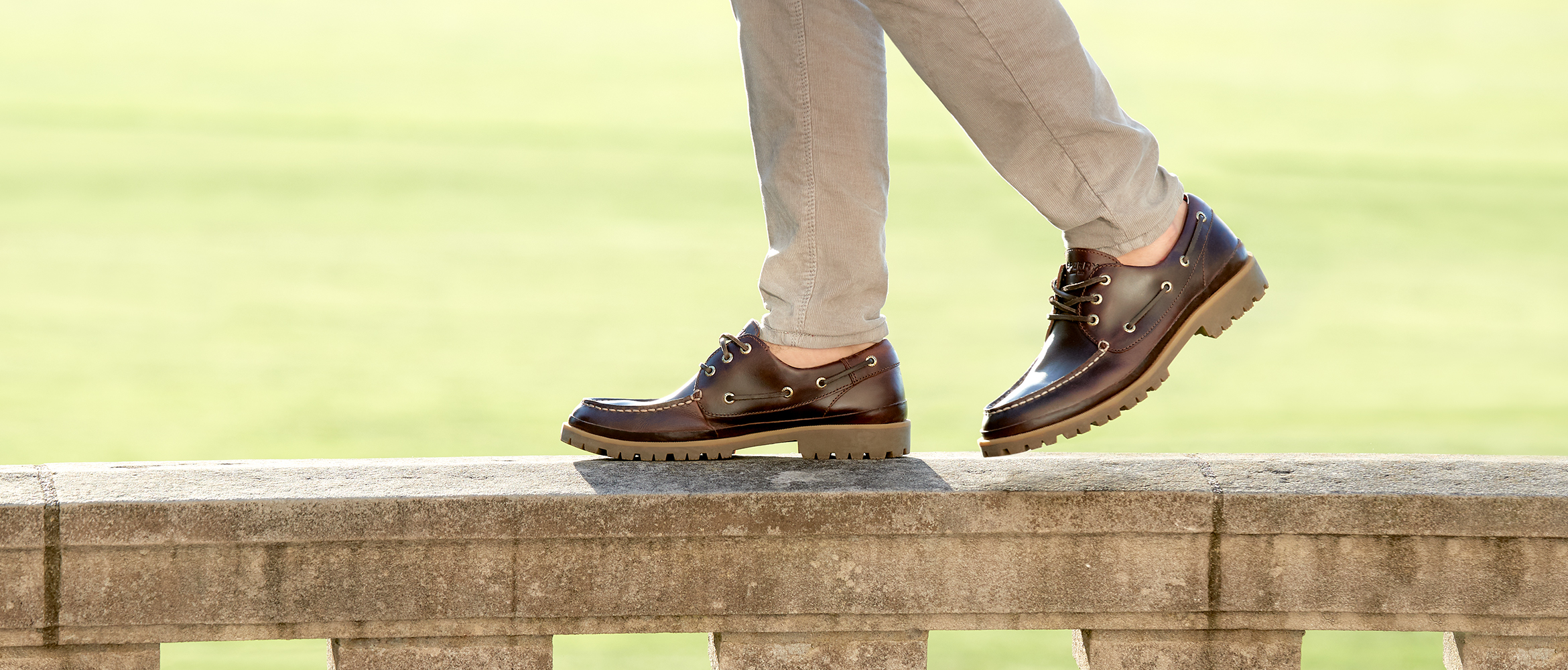 Close up of men's lug boat shoes walking precariously along a stone railing.