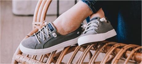 A woman sitting on a wicker bench, wearing Sperry sneakers.