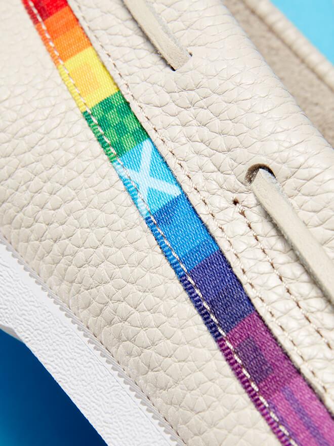 Cream leather shoe with rainbow semaphore flag accent.
