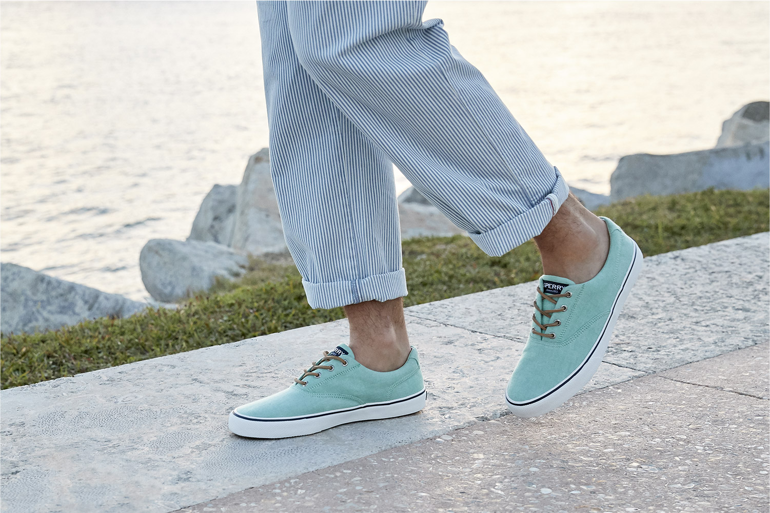 Man's leg wearing teal-colored striper sneakers overlooking the water