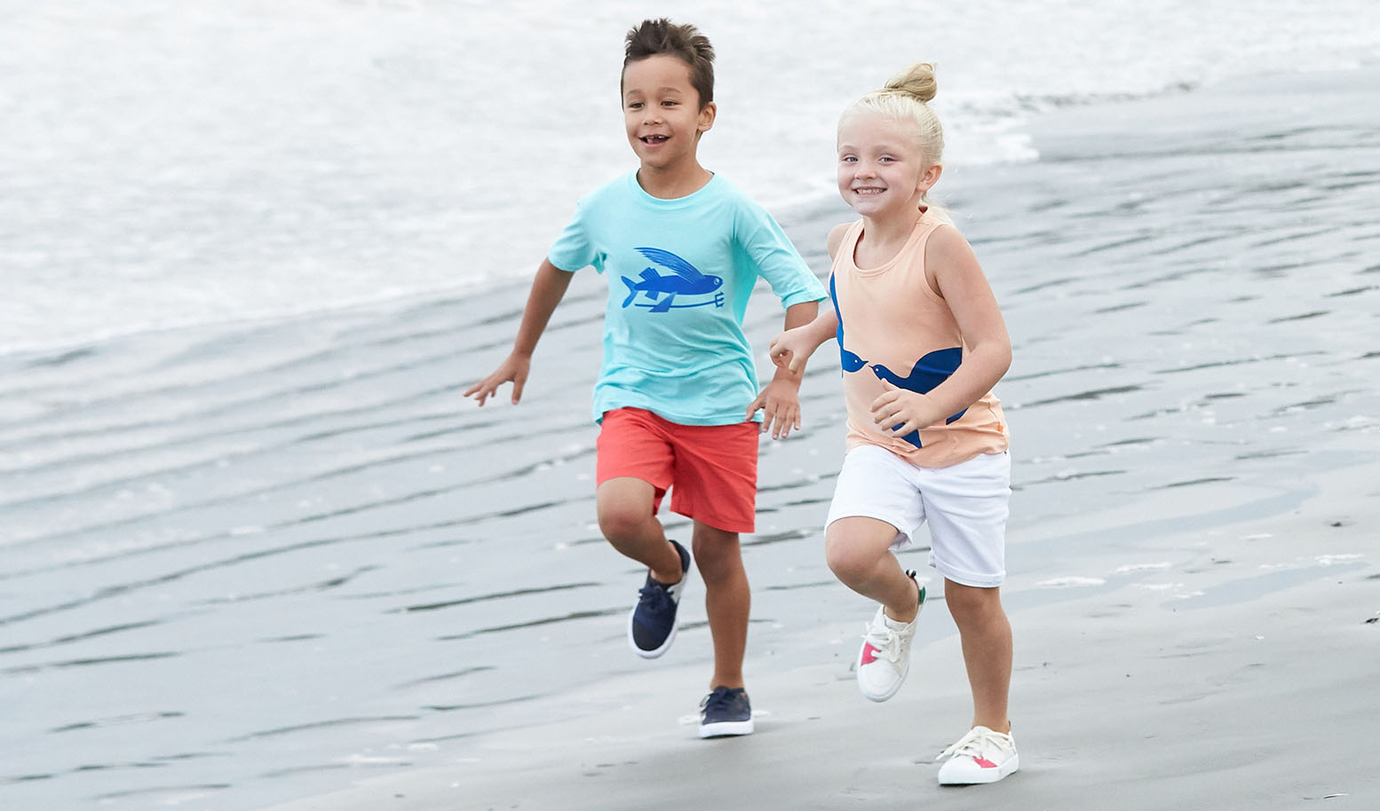 A boy and a girl are laughing as they run along the shoreline.