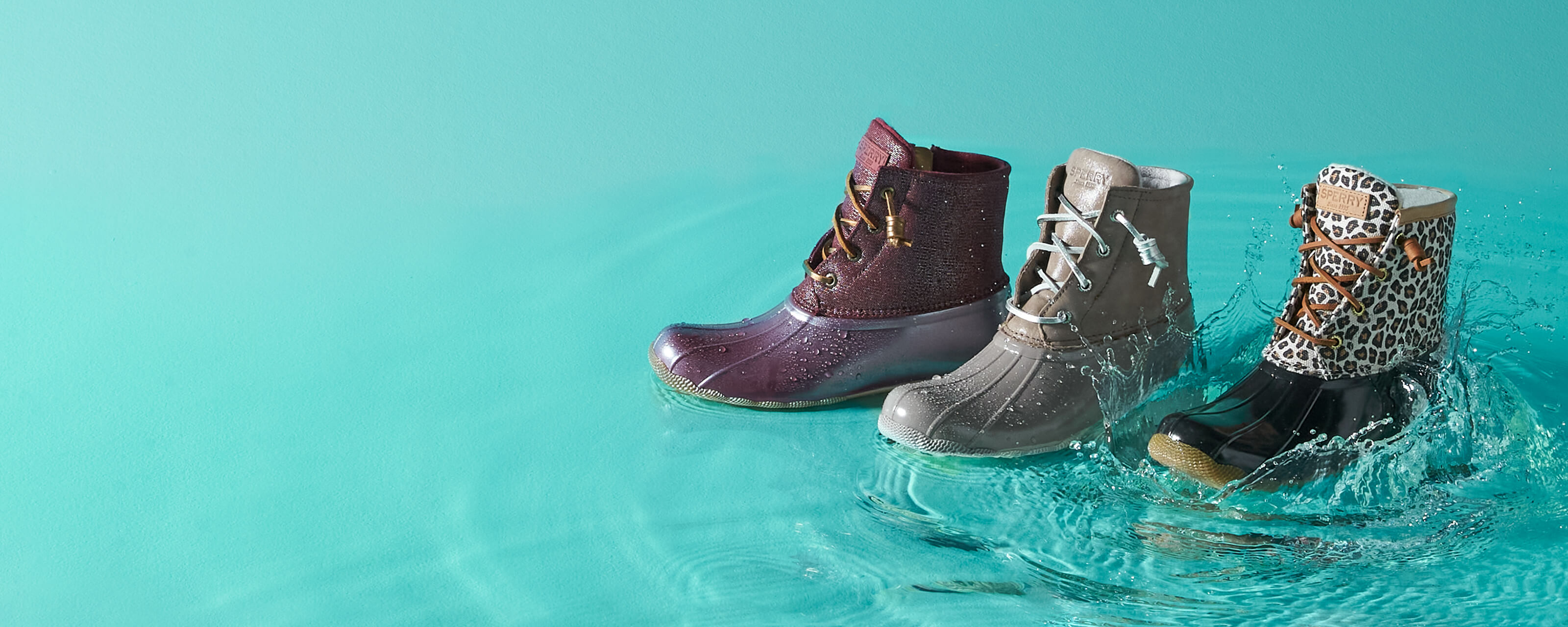 Three Saltwater boots standing in a puddle.