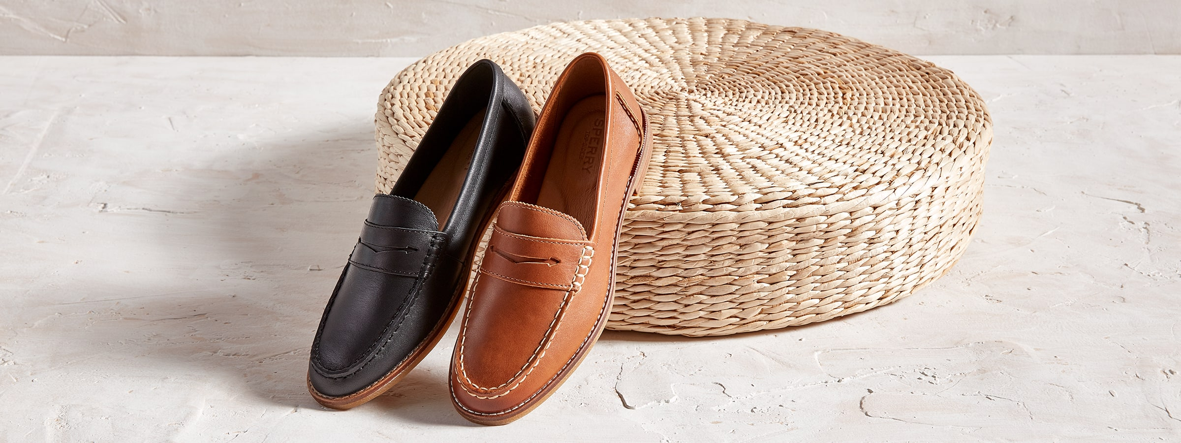 2 Sperry Loafers propped up on a basket.