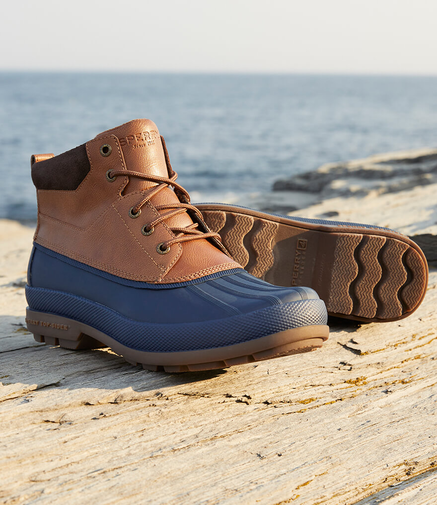 Boots on driftwood beside the ocean.