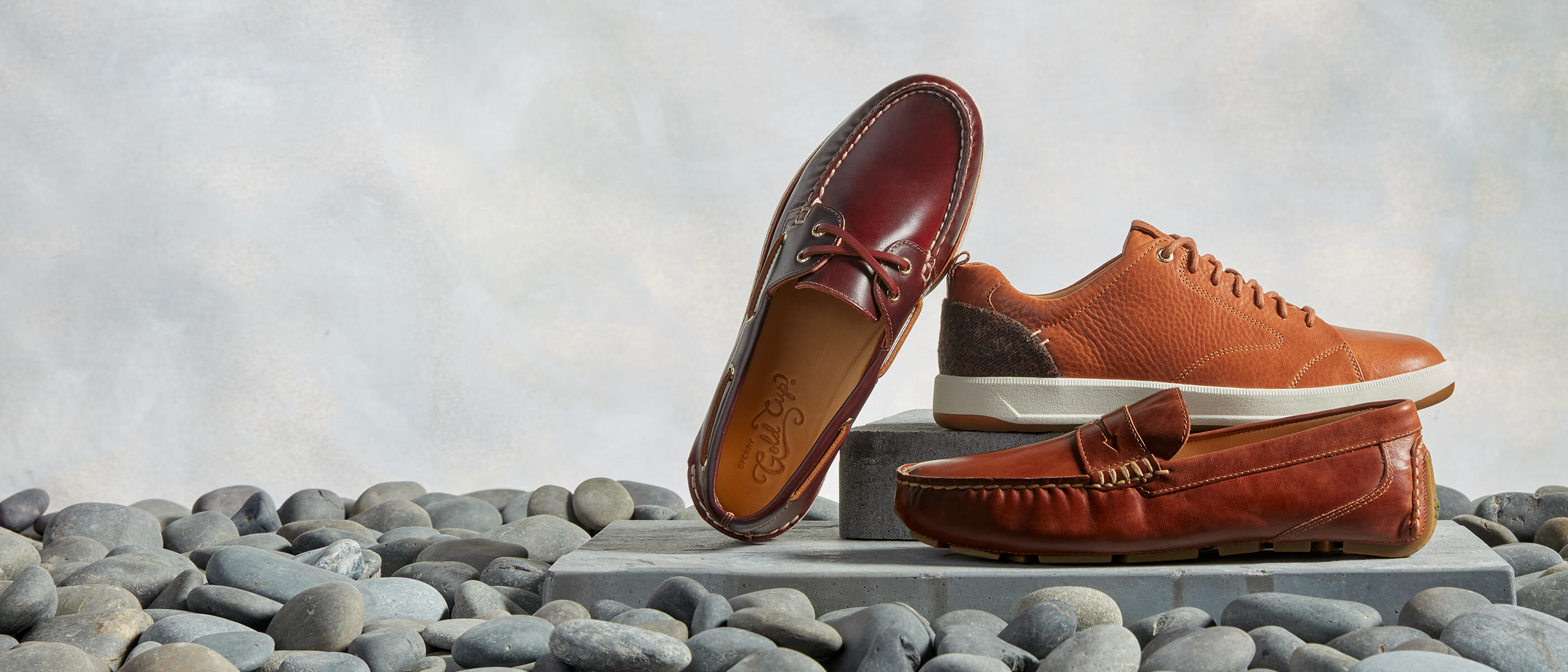 Brown Sperry Gold Cup shoes on a concrete slab surrounded by grey river stones.