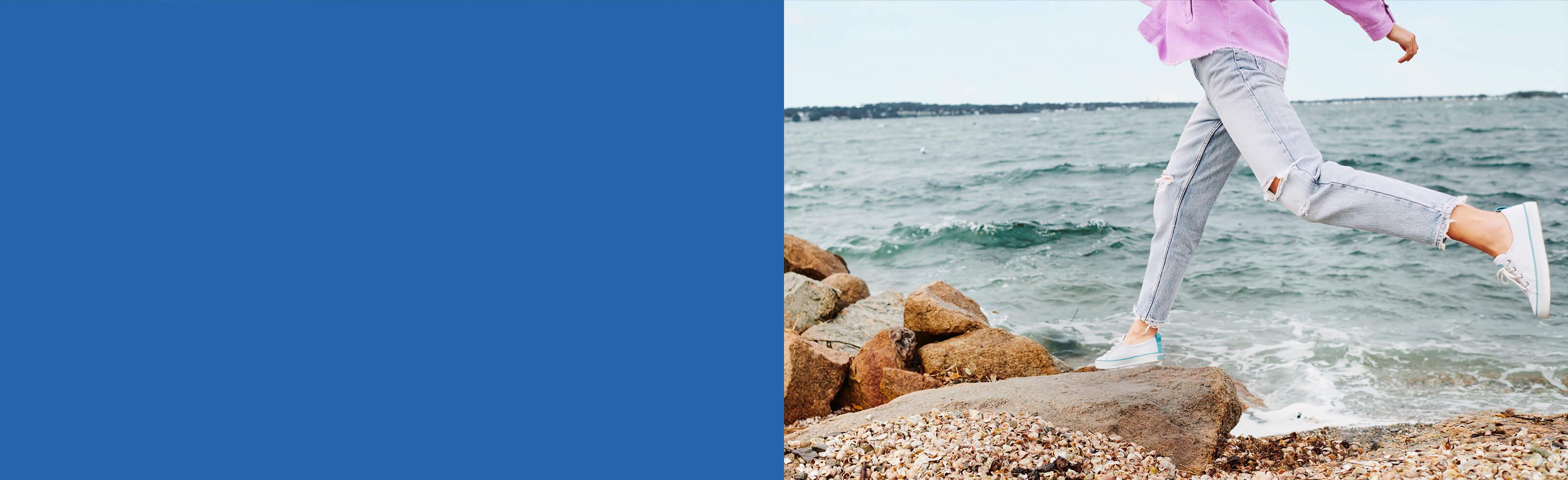 Running over sand and rocks beside the ocean.