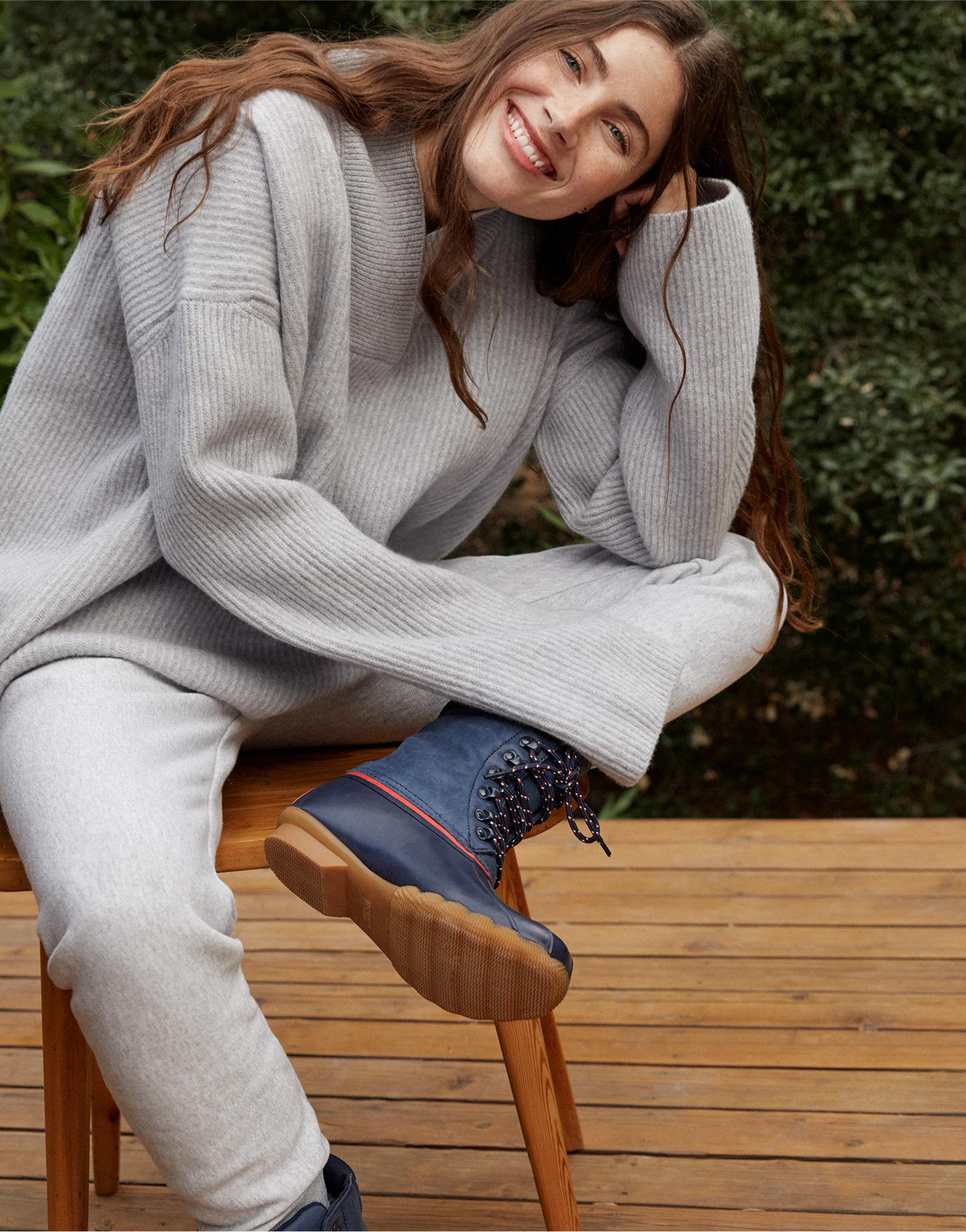 Woman wearing Goop & Sperry boots while sitting on a stool smiling.