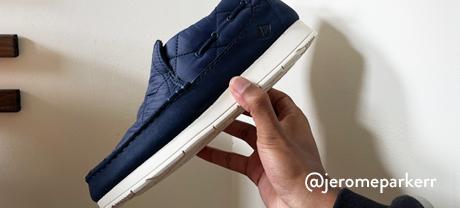 A hand holds a blue shoe aloft.